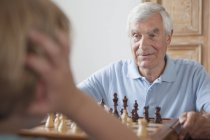 Senior man playing chess with grandson at home — Stock Photo