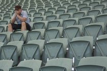 Sad man sitting alone in empty stadium — Stock Photo