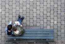 Zwei jungen auf Parkbank sitzen und mit Blick auf Buch — Stockfoto