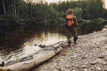 Vue arrière du randonneur debout au bord de lac en bois — Photo de stock