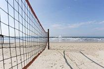 Волейбольная сетка на пляже на солнечном песке — стоковое фото