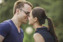 Side view of couple rubbing noses in park — Stock Photo