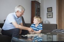 Happy grandson and grandfather looking at each other while solving jigsaw puzzle in living room — Stock Photo