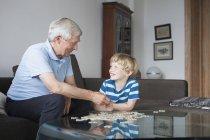 Heureux petit-fils et grand-père se regardant tout en résolvant puzzle dans le salon — Photo de stock