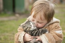 Bambino ragazza tenendo gatto e baciare all'aperto — Foto stock