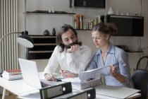 Focused couple working with laptop at home — Stock Photo