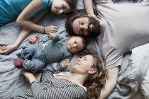 Портрет щаслива родина, відпочиваючи на ліжко разом — стокове фото