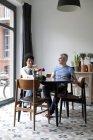 Веселая смешанная возрастная пара, наслаждающаяся завтраком вместе в столовой — стоковое фото