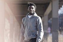 Портрет молодої людини, що стоїть на спортивні передачі під мостом міста — стокове фото