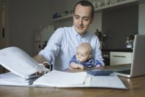 Pai fazendo papelada enquanto carrega menino em casa — Fotografia de Stock