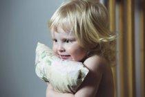 Rubia niña abrazando almohada en casa - foto de stock