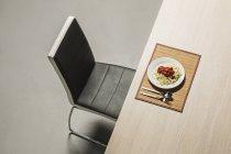 Spaghetti con sugo di pomodoro fresco servita sul tavolo di fronte a sedia moderna — Foto stock