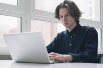 Confident young man using laptop at a desk — Stock Photo