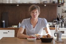 Портрет молодого человека, сидел за обеденным столом с завтраком — стоковое фото