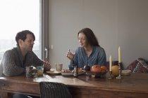 Couples ayant le petit déjeuner à la table à manger en bois — Photo de stock