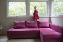 Girl standing on pink sofa by window at home — Stock Photo