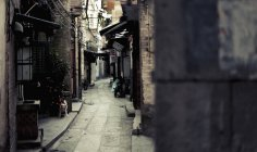 View to narrow lane between shabby brick houses — Stock Photo