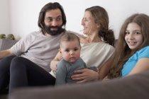 Famille avec deux enfants se relaxant dans le salon — Photo de stock