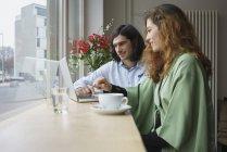 Amigos sonrientes tomando café mientras uso la laptop en café - foto de stock