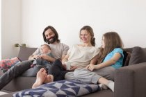Family with two children relaxing in living room — Stock Photo