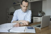 Homem sério trabalhando com laptop e arquivo em casa — Fotografia de Stock