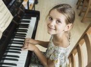 Retrato de alto ángulo de la niña tocando el piano en casa - foto de stock
