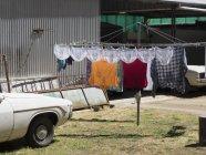 Linge séchant sur la corde à linge à yard avec des voitures garées — Photo de stock
