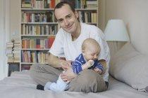 Vater und Sohn sitzen zu Hause im Bett gegen Bücherregal — Stockfoto