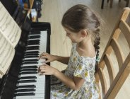 Blick aus der Vogelperspektive auf Mädchen, die zu Hause Klavier spielen — Stockfoto