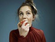 Giovane donna mangiare mela su sfondo blu — Foto stock