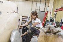 Female mechanic repairing car at repair shop — Stock Photo