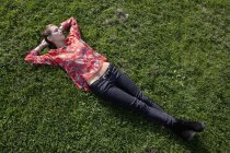 Young thoughtful woman lying on grass in park — Stock Photo