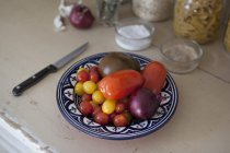 Close up view of various tomatoes with onion in plate — Stock Photo