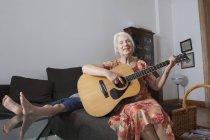 Senior mujer canto y guitarra en casa con su nieto en el fondo - foto de stock