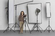 Longitud total de confianza madura mujer fotógrafo en estudio fotográfico - foto de stock