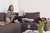 Donna che utilizza il computer portatile sul divano in soggiorno — Foto stock