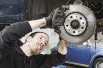 Sorridente lavoratore maschile riparazione auto in officina di riparazione auto — Foto stock