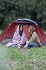 Junges Paar sitzt neben Kuppelzelt in der Natur — Stockfoto