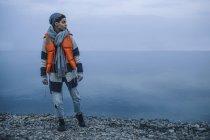 Adolescente portant gilet de sauvetage debout sur la rive du lac et regardant loin — Photo de stock