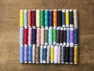 Reihen von verschiedenen farbigen Spulen des Fadens auf Holztisch — Stockfoto