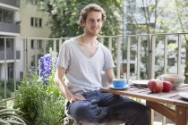 Portrait of smiling man having breakfast at porch — Stock Photo