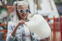 Moda joven mujer en gafas de sol comiendo algodón de azúcar al aire libre - foto de stock