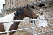 Девушка, обнимающая лошадь на ферме — стоковое фото
