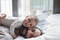 Портрет любящего отца с девочкой, лежащей в постели — стоковое фото