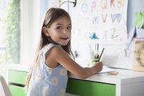 Portrait de fille heureuse faisant ses devoirs au bureau — Photo de stock