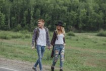 Couple holding hands while walking on roadside near forest — Stock Photo