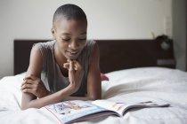 Молодая женщина читает журнал в спальне дома — стоковое фото