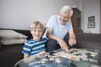 Glücklicher Enkel und Großvater sitzt mit Puzzle im Wohnzimmer — Stockfoto