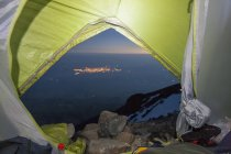 Landscape with illuminated city at distant seen from tent on mountain at dusk — Stock Photo