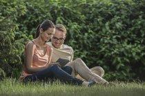 Пара, использующая цифровой планшет вместе, сидя на траве в парке — стоковое фото